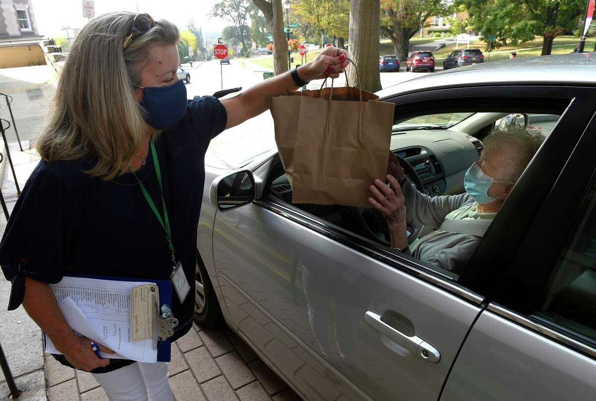 Deana Salerno, administrative staff assistant for the Greenwich Commission on Aging, hands a lunch to Josephine Kulesh as she, along with several Greenwich seniors arrive to pick up a meal during Teddy's Ready Drive Thru Lunch at the Greenwich Senior Center on Sept. 25, 2020 in Greenwich, Connecticut. Those seniors who participated in the monthly luncheon were treated to BBQ Ribs, along with a serving of Mac and Cheese, Sauted Green Beans and Carrots and a Lemon Bar with a Raspberry Sauce. Over 120 meals were prepared by Chef Teddy Teddy Torchon and his crew. Also, senior received packets of the Flagship edition of the