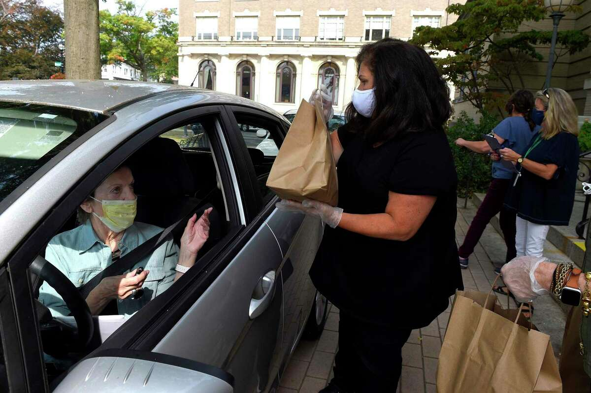 Rita Cody directs Lori Contadino, Director for the Greenwich Commission on Aging, on where to put lunches for seniors that carpool with her to pick up a meal during Teddy's Ready Drive Thru Lunch at the Greenwich Senior Center on Sept. 25, 2020 in Greenwich, Connecticut. Those seniors who participated in the monthly luncheon were treated to BBQ Ribs, along with a serving of Mac and Cheese, Sauted Green Beans and Carrots and a Lemon Bar with a Raspberry Sauce. Over 120 meals were prepared by Chef Teddy Teddy Torchon and his crew. Also, senior received packets of the Flagship edition of the