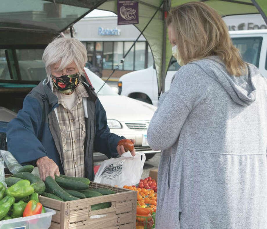 Vendor Linda Mueller packages vegetables for a customer. Photo: Rochelle Eiselt | Journal-Courier