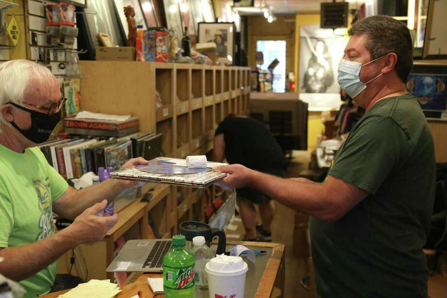 Johnny's Records in Darien celebrated a new format of Record Store Day. Sean Moran of Stratford, right, makes a purchase from John Konrad, who opened his legendary store Johnny's in October, 1975. Photo: Jarret Liotta /Hearst Connecticut Media /