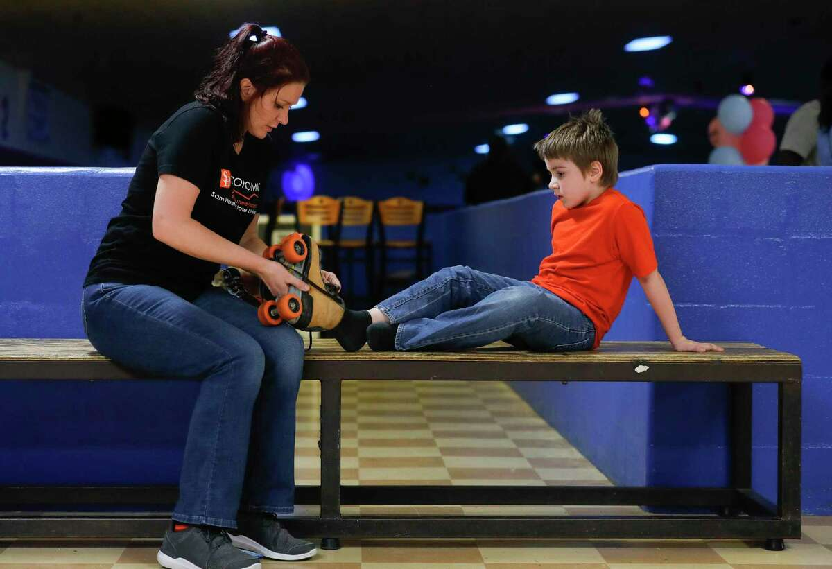 Ai'mee Rodgers helps her autistic son, Rion Bailey, with his skates during a fundraiser for the her and her three children at Rainbow Roller Rink, Saturday, Sept. 26, 2020, in Conroe. The event raised money for the family after their home caught fire on Aug. 4.