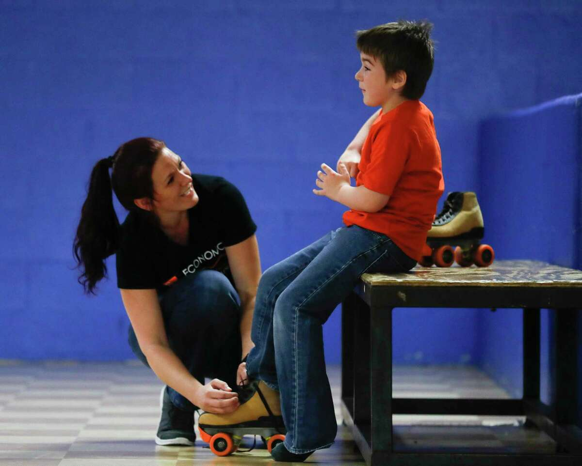 Ai'mee Rodgers shares a laugh with her son Rion Bailey, as she helps him put on skates during a fundraiser for the her and her three children at Rainbow Roller Rink, Saturday, Sept. 26, 2020, in Conroe. The event raised money for the family after their home caught fire on Aug. 4.