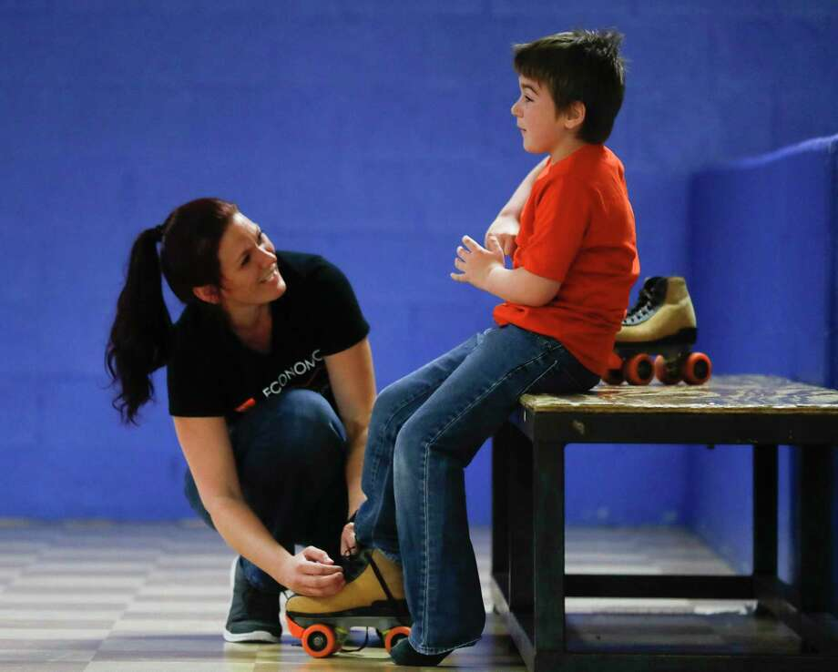 Ai'mee Rodgers shares a laugh with her son Rion Bailey, as she helps him put on skates during a fundraiser for the her and her three children at Rainbow Roller Rink, Saturday, Sept. 26, 2020, in Conroe. The event raised money for the family after their home caught fire on Aug. 4. Photo: Jason Fochtman, Houston Chronicle / Staff Photographer / 2020 © Houston Chronicle