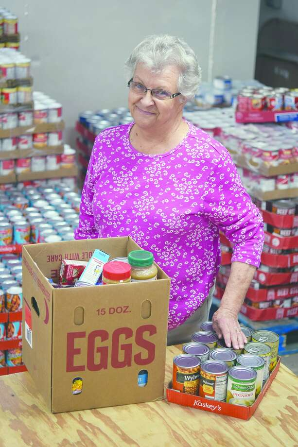Cass County Food Pantry director Joanne Anderson with a box of food that will be part of September's distribution to needy county residents. Photo: David Blanchette | Journal-Courier