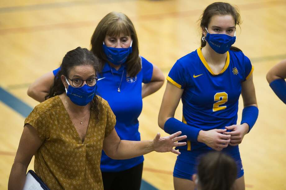 Midland High volleyball coach Angela McMath (left) talks with her team, including daughter Olivia (2), during a Sept. 24, 2020 match against Saginaw Heritage. Photo: Katykildee/kildee@mdn.net