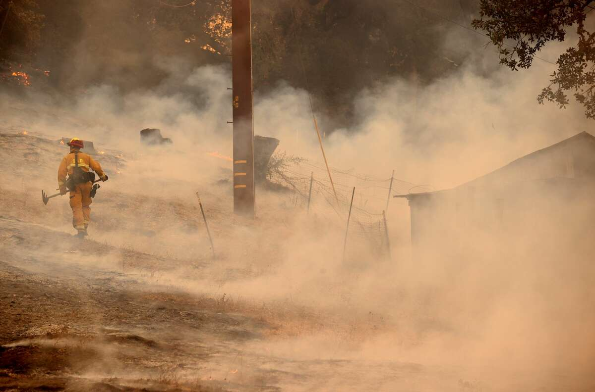 A firefighter walks through smoke as he battles the Glass Fire on September 27, 2020 in Napa, California. The fast moving Glass fire has burned over 1,000 acres, prompting evacuations. Much of Northern California is under a red flag warning for high fire danger through Monday evening. (Photo by Justin Sullivan/Getty Images)