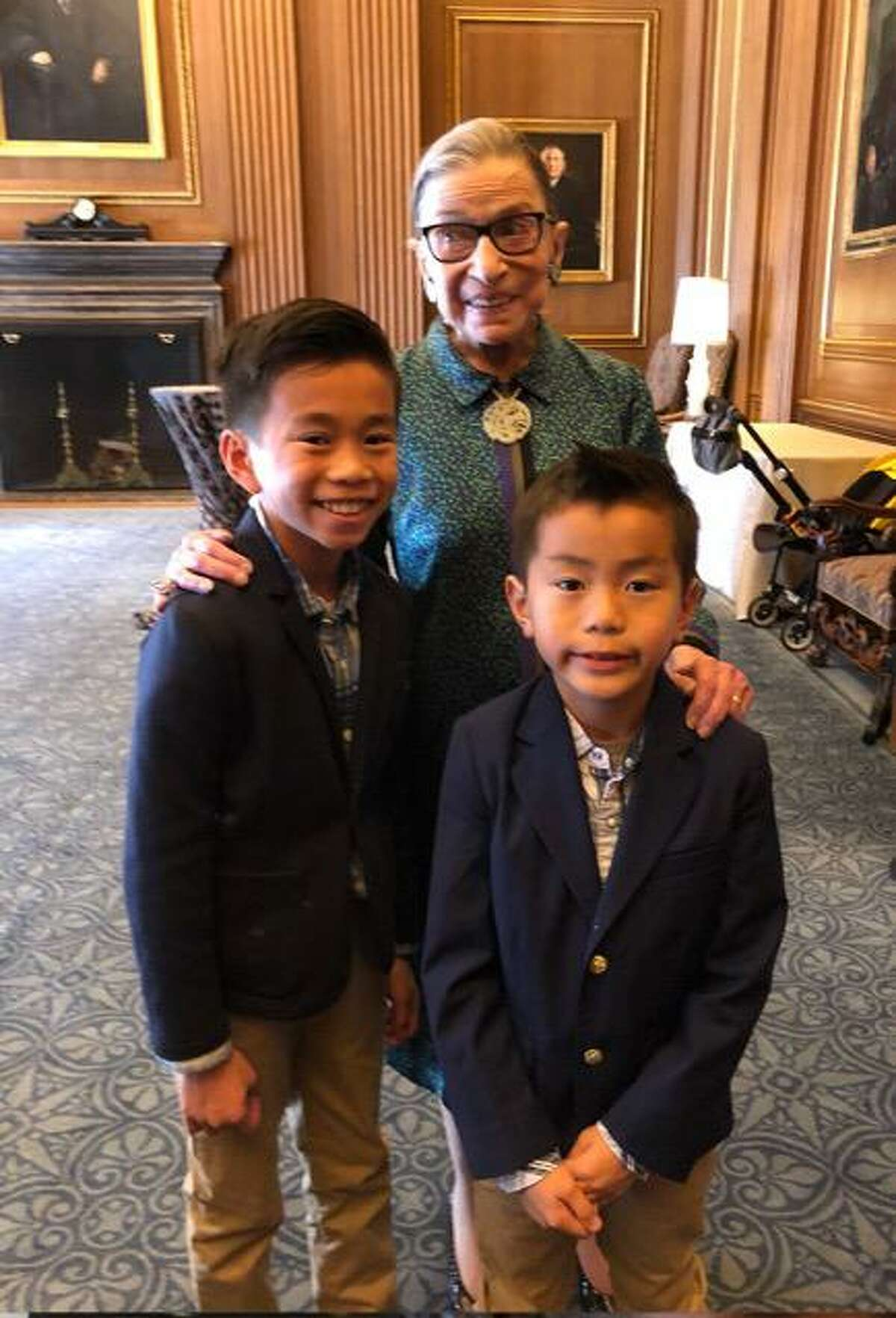 Justice Ginsburg with Michael Li-Ming Wong's children, Caleb Wong and Jacob Wong, in 2018 at the Supreme Court.