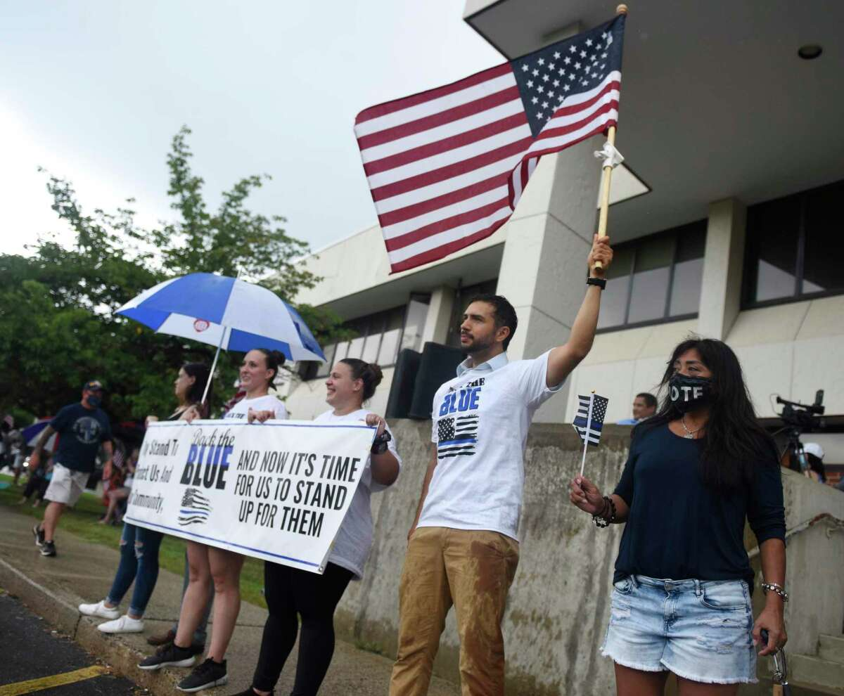 State Rep. candidate JD Ospina waves a flag with others during the police rally at the old Stamford Police Station in Stamford, Conn. Sunday, Aug. 2, 2020. Hundreds endured the ceremony through the rain to show their appreciation for the Stamford Police Department.