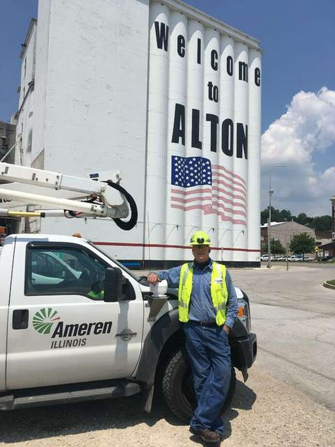 Scott Walsh, of Ameren Illinois, is shown outside his truck in Alton. At 53, Walsh is currently doing basically the same job and shift that his dad, Marty, had before he retired.