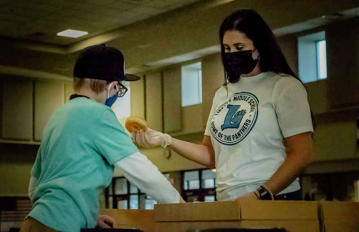 Liberty Middle School counselor and FIT/GO supervisor Kaitlyn Talley begins to hand over a donut to a Liberty student as part of the school's fundraising effort for Paint The Town Gold Thursday morning.