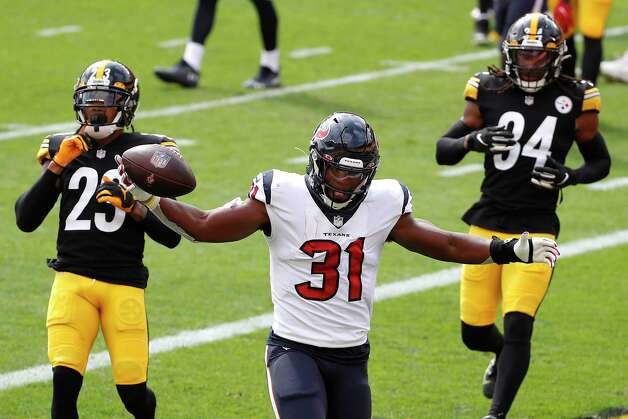 Houston Texans running back David Johnson (31) runs past Pittsburgh Steelers cornerback Joe Haden (23) and strong safety Terrell Edmunds (34) into the end zone for a 2-yard touchdown run during the first half of an NFL football game at Heinz Field on Sunday, Sept. 27, 2020, in Pittsburgh. Photo: Brett Coomer, Staff Photographer / © 2020 Houston Chronicle