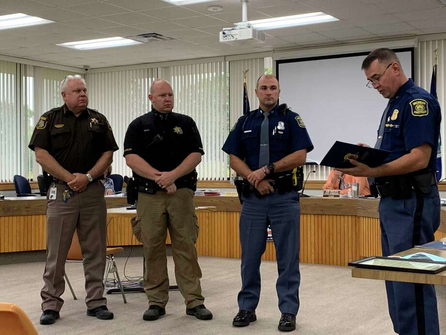 Benzie County Sheriff Ted Schendel (left) looks on as deputyJoseph Send and Michigan State Police trooper Charles Sierzputowskiwere recognized on Sept. 22 byCadillac Post Commander Frank Keck with awards for saving a man's life. (Courtesy Photo)