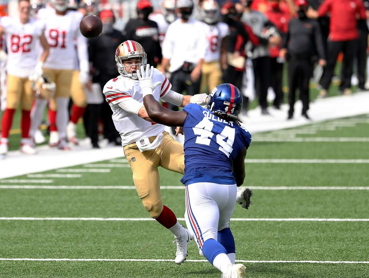 Nick Mullens #4 of the San Francisco 49ers passes under pressure from Markus Golden #44 of the New York Giants in the first quarter at MetLife Stadium on September 27, 2020 in East Rutherford, New Jersey.