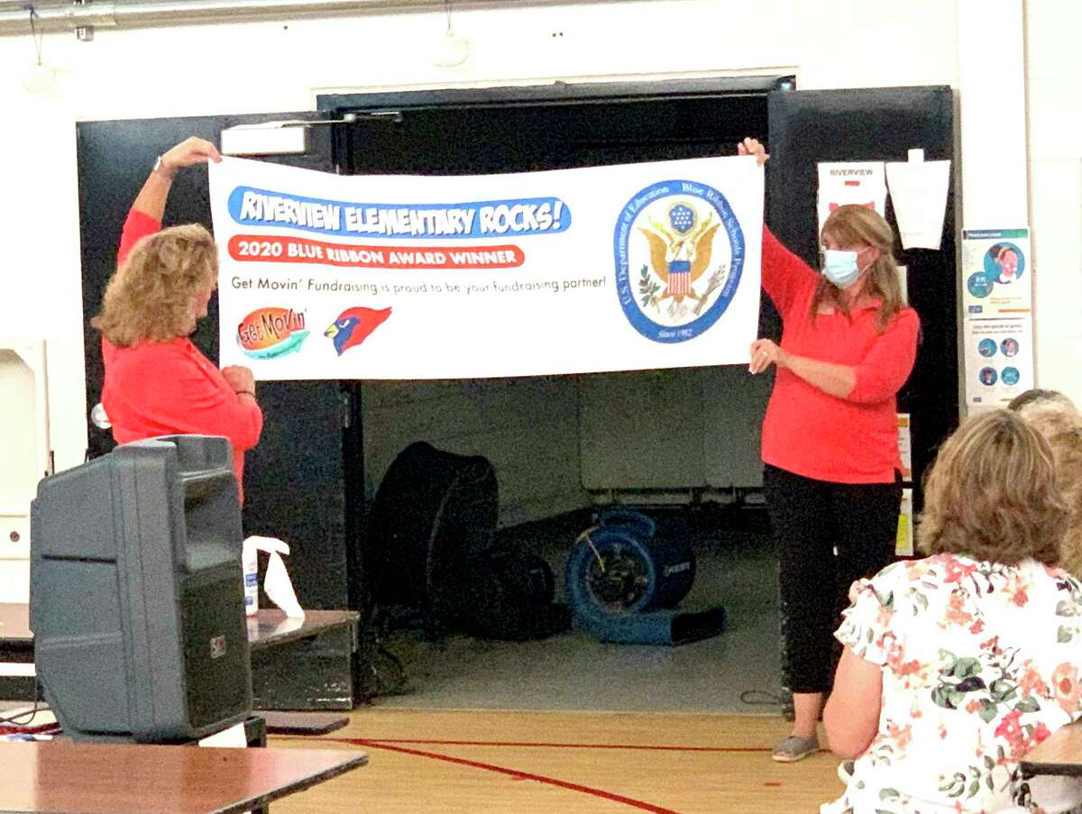 Riverview Elementary staff were shocked after hearing the news their school won the National Blue Ribbon Award. Staff members unveiled a banner recognizing the school's accomplishment. (Courtesy photo)