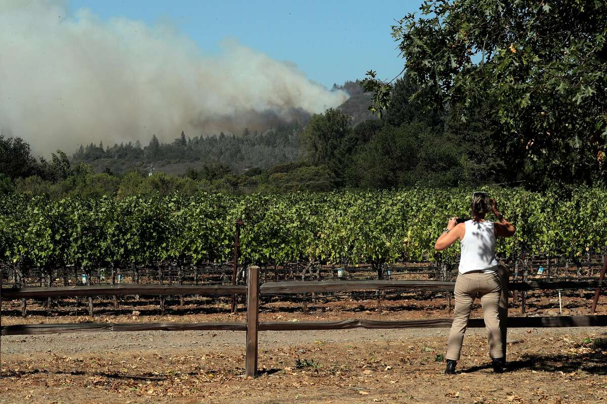 Carol Ort stops on White Cottage Road to photograph the smoke plume as the Glass fire burned north of St. Helena, Calif., on Sunday, September 27, 2020.