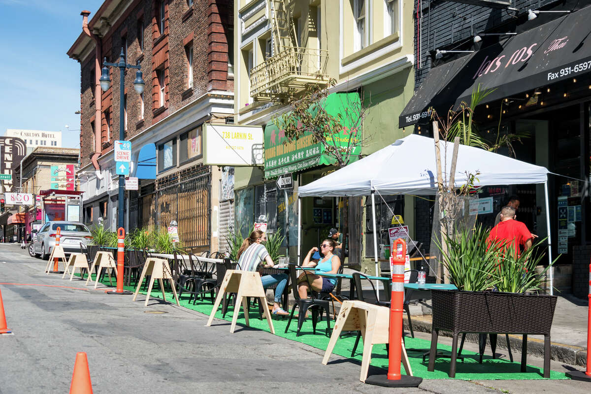 Diners sit at outdoor tables on a closed street, enjoying the food at Lers Ros Thai, Turtle Tower, Pho 2000 and other restaurants. As San Francisco moves into the orange tier, restaurants can open for indoor dining, but experts urge caution.