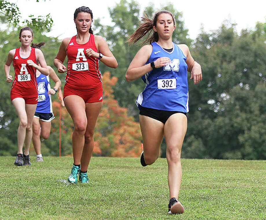 Marquette Catholic senior Megan Jarzenbeck (right) leads Alton's Eva Schwaab (middle) and Maya Grassel to a downhill slope in the first mile of the Alton Invitational cross country meet Wednesday at Moore Park in Alton. Photo: Greg Shashack / The Telegraph