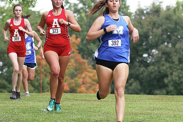 Marquette Catholic senior Megan Jarzenbeck (right) leads Alton's Ava Schwaab (middle) and Maya Grassel to a downhill slope in the first mile of the Alton Invitational cross country meet Wednesday at Moore Park in Alton.