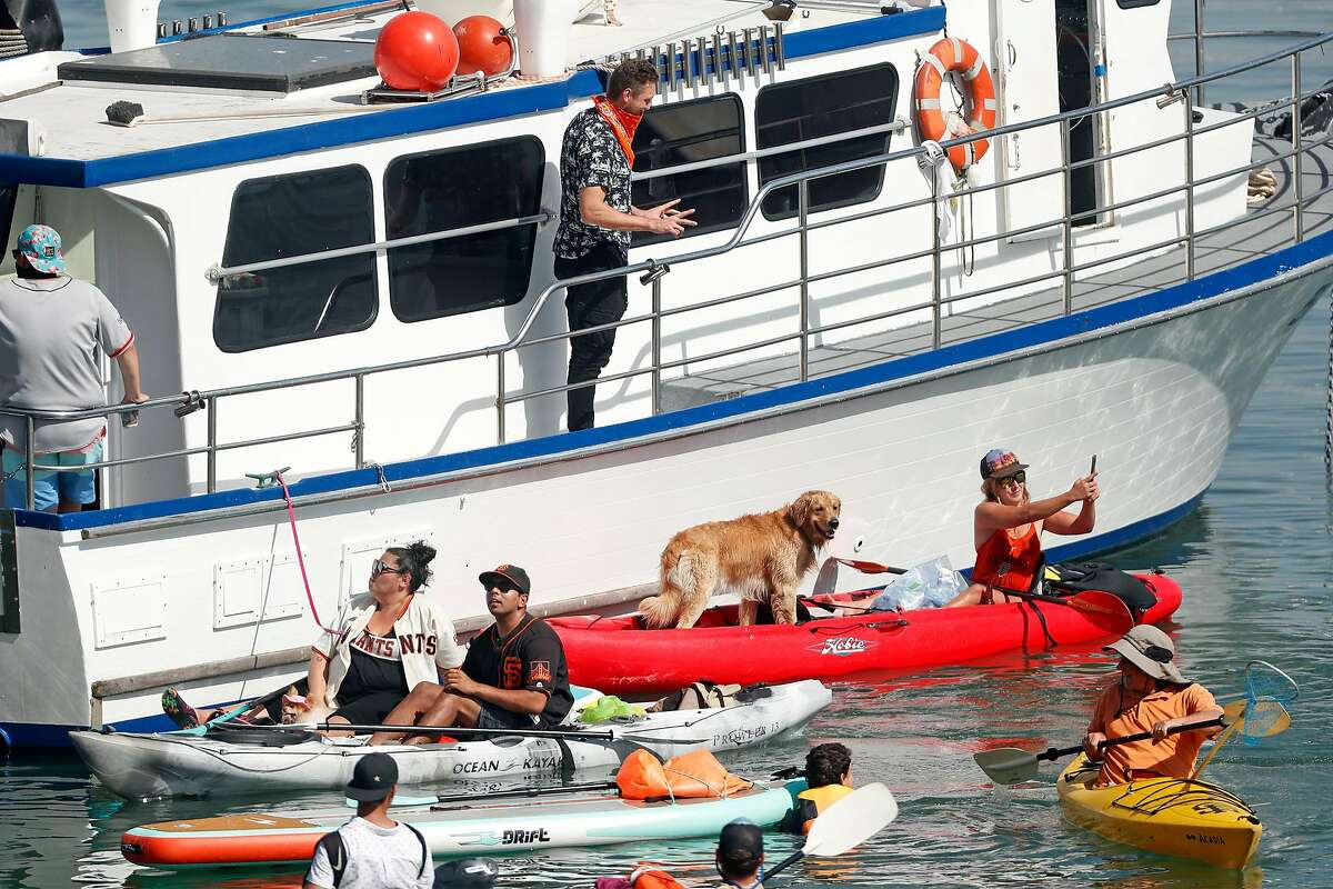 Hunter Pence spent the final day of the 2020 regular season on a boat in McCovey Cove cheering on the Giants, signing autographs and - as shown here - posing for pictures.