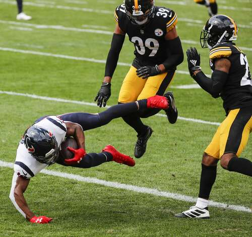Houston Texans wide receiver Randall Cobb (18) dives between Pittsburgh Steelers free safety Minkah Fitzpatrick (39) and cornerback Steven Nelson (22) for a 28-yard touchdown reception during the first half of an NFL football game at Heinz Field on Sunday, Sept. 27, 2020, in Pittsburgh. Photo: Brett Coomer/Staff Photographer / © 2020 Houston Chronicle