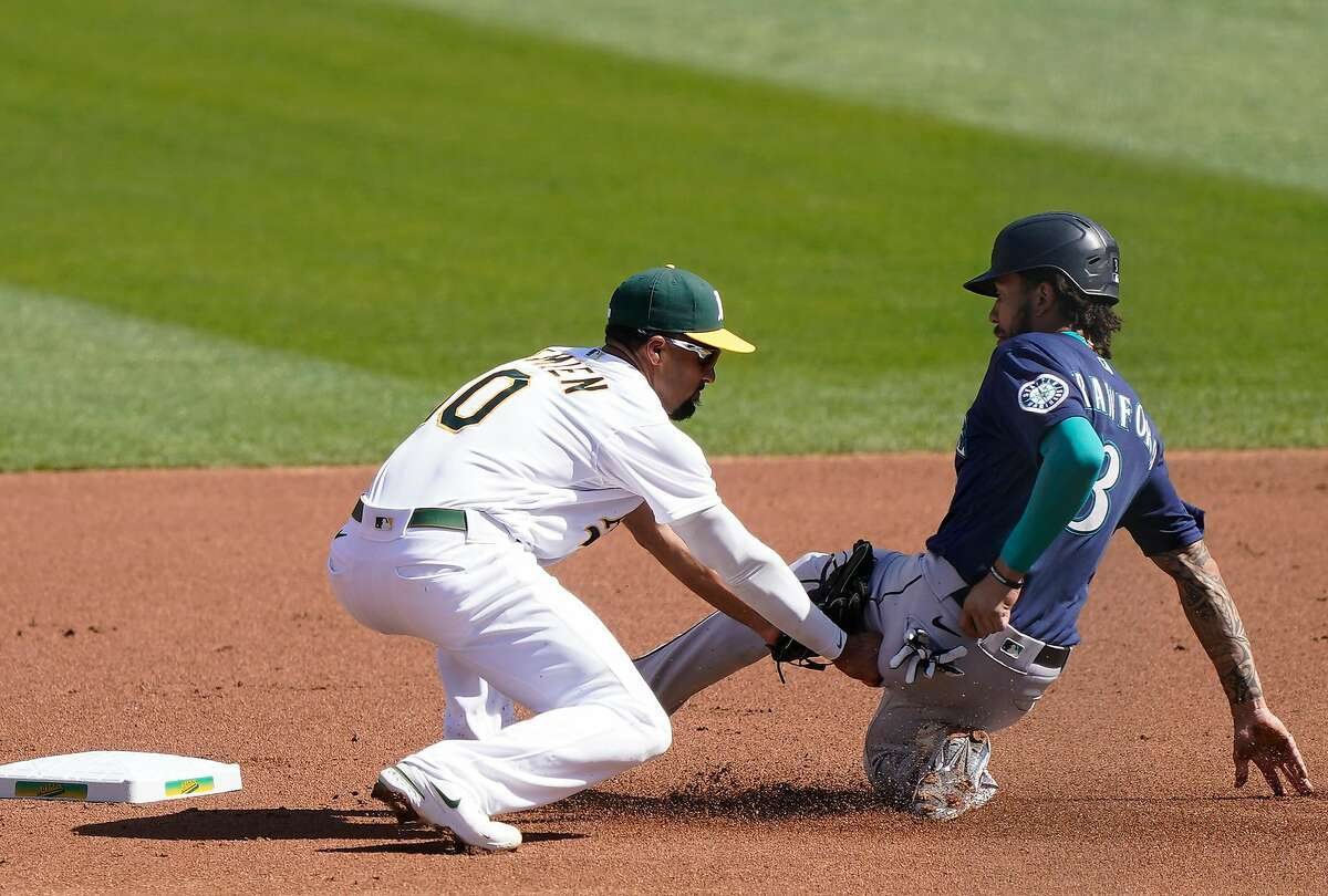 J.P. Crawford attempts to steal second base in front of Marcus Semien during the A's 6-2 win at RingCentral Coliseum.