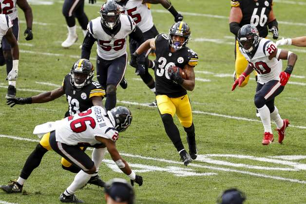 Pittsburgh Steelers running back James Conner (30) runs past Houston Texans outside linebacker Whitney Mercilus (59) and strong safety Justin Reid (20) for a first down during the fourth quarter of an NFL football game at Heinz Field on Sunday, Sept. 27, 2020, in Pittsburgh. Photo: Brett Coomer/Staff Photographer / © 2020 Houston Chronicle