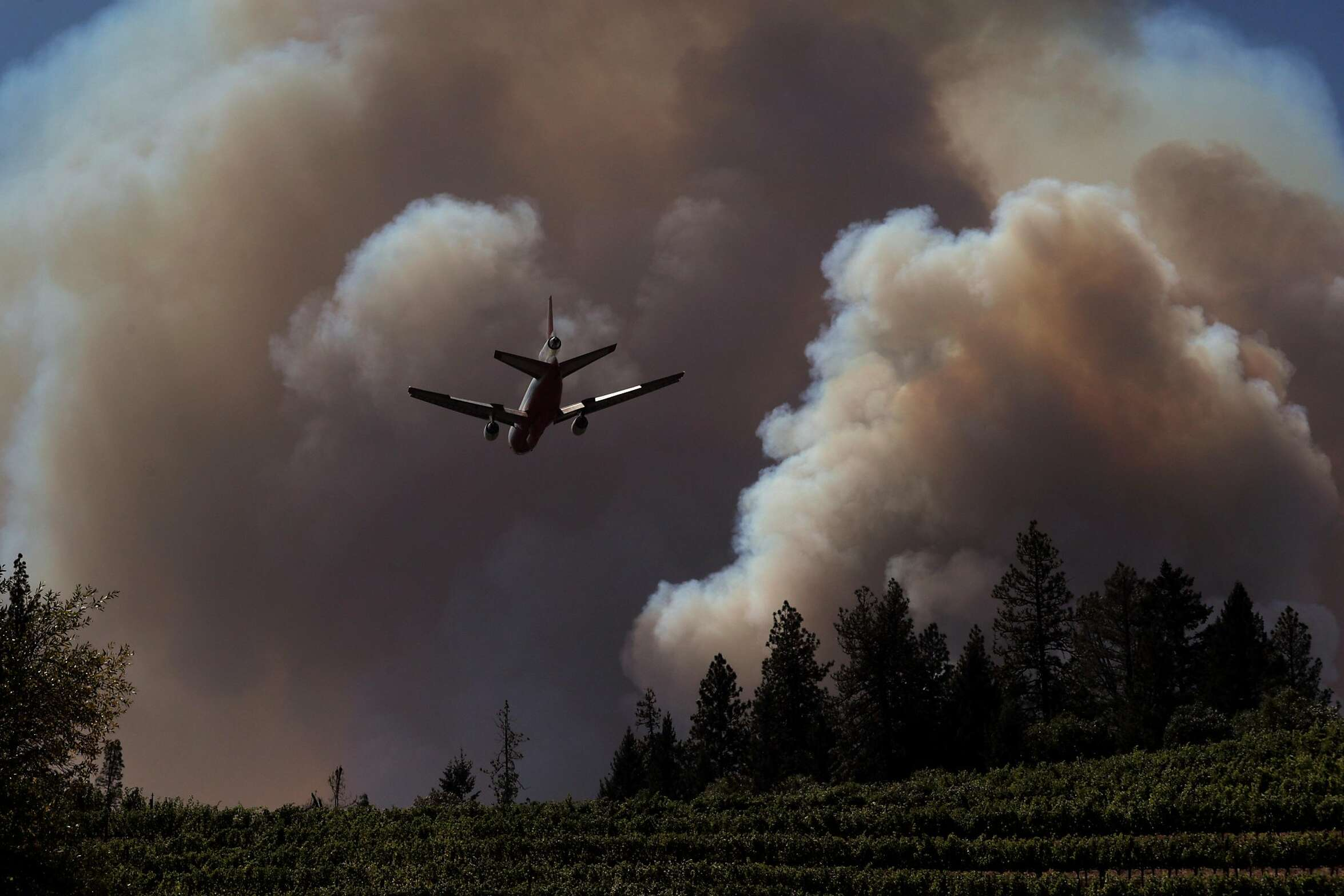 A tanker flies toward their drop point over Bell Canyon as the Glass fire burned north of St. Helena, Calif., on Sunday, September 27, 2020.