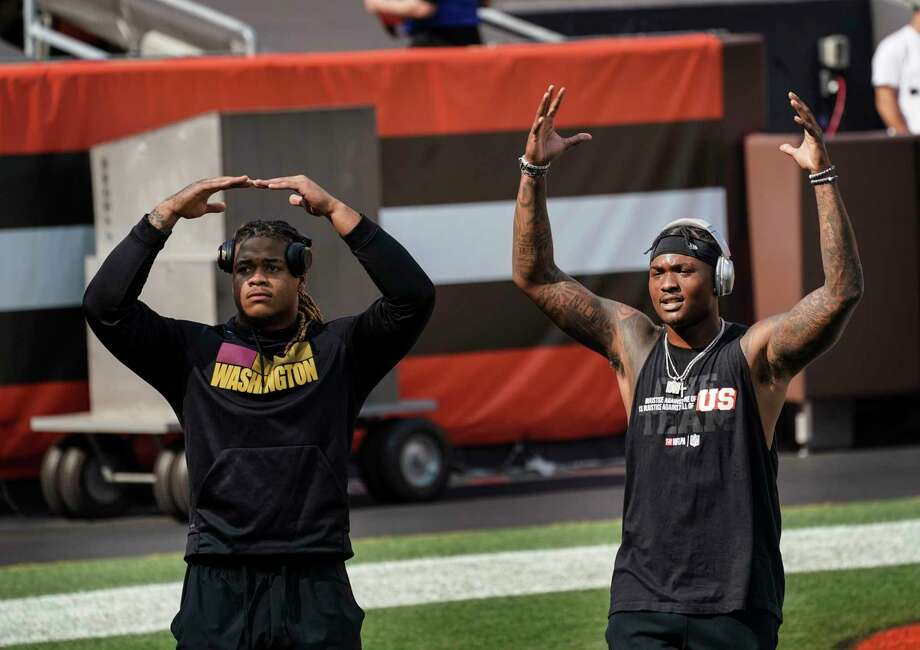Washington Football Team defensive end Chase Young, left, and quarterback Dwayne Haskins, both former Ohio State University players, make make an O and H gesture to fans before the game with the Browns in Cleveland on Sunday, Sept. 27, 2020. Photo: Washington Post Photo By Toni L. Sandys / The Washington Post