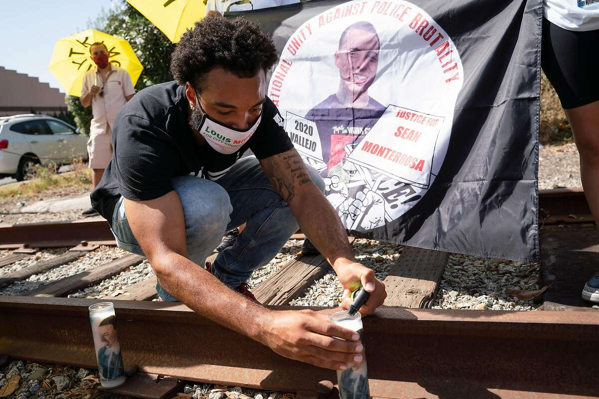Vallejo City Council candidate Louis Michael lights a candle in honor of Sean Monterrosa.