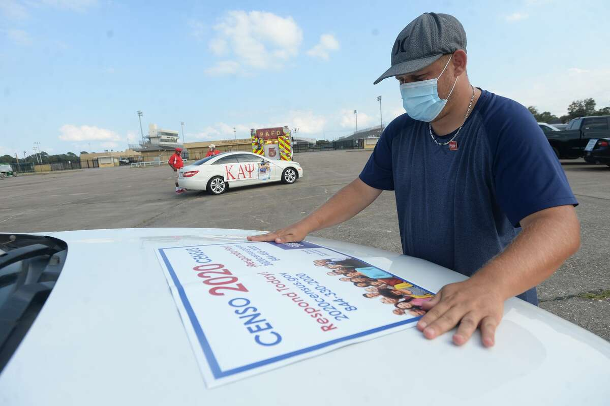 Michael Joshlin lines up a magnetic placard to decorate a vehicle as he and other workers and supporters prepare for a Census 2020 caravan in Port Arthur Friday. The event is one of the last in the region as census workers make a final push to increase count numbers in low-return areas like Port Arthur before the latest September 30 deadline. Photo taken Friday, September 25, 2020 Kim Brent/The Enterprise