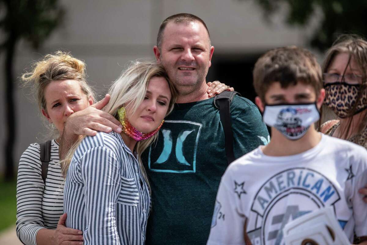 Morgan Atkins is embraced by her father, Arvel Whitner, and her mother, Mary Whitner, as a bus carrying Atkins' husband, Sgt. 1st Class Sean Atkins. leaves Kelly Reeves Stadium on Sunday, Sept. 27, 2020.