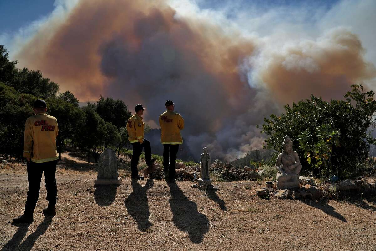 Firefighters keep an eye on fire progress from Viader Vineyards & Winery as the Glass fire burns near Bell Canyon Reservoir north of St. Helena, Calif., on Sunday, September 27, 2020.