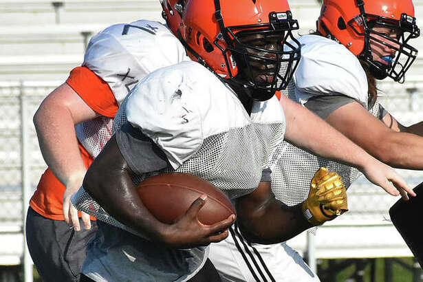 Edwardsville running back Justin Johnson Jr. takes the handoff in the backfield during a practice in the summer inside the District 7 Sports Complex.