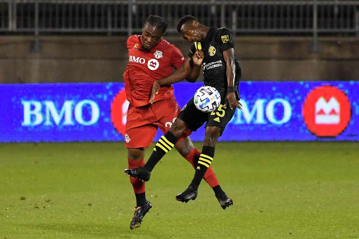 Toronto FC's Ayo Akinola, left, collides with the Columbus Crew's Harrison Afful during a Sept. 27 match in East Hartford.