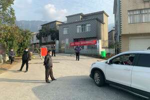 Farmers near China's Hubei province watch a checkpoint outside their village to stop people from entering in February 2020.