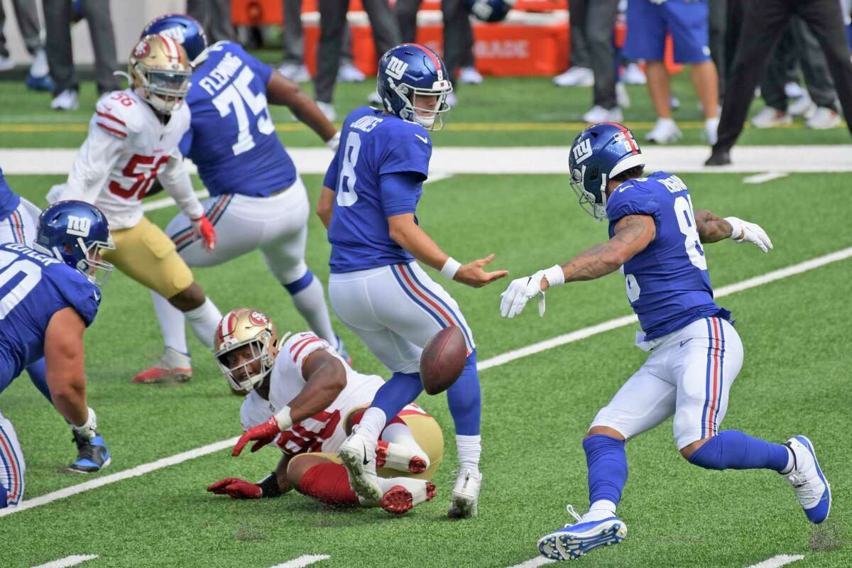 New York Giants quarterback Daniel Jones, center, and San Francisco 49ers' Kevin Givens (90) looks after a loose ball during the first half of an NFL football game, Sunday, Sept. 27, 2020, in East Rutherford, N.J. (AP Photo/Bill Kostroun)