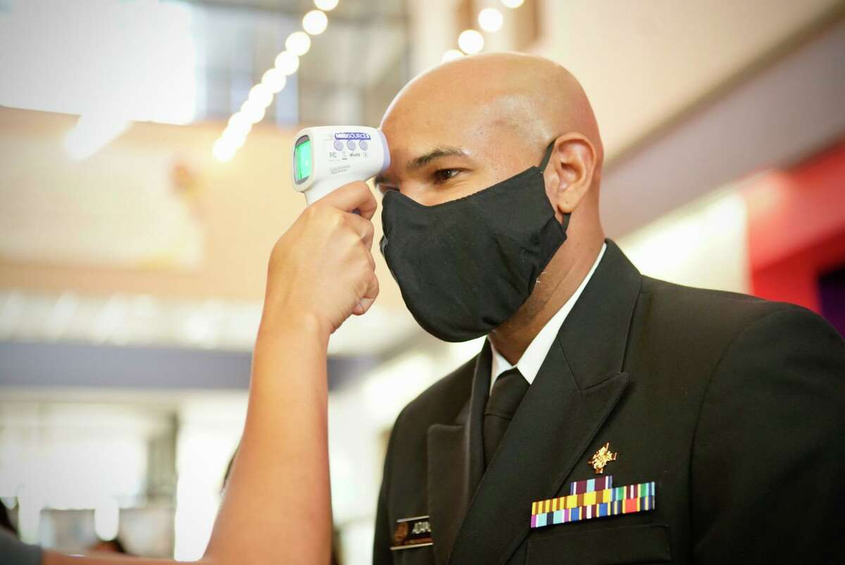 U.S. Surgeon General Jerome Adams has his temperature checked before a meeting with local political and health officials at The Health Museum on Sunday, Sept. 26, 2020, in Houston.