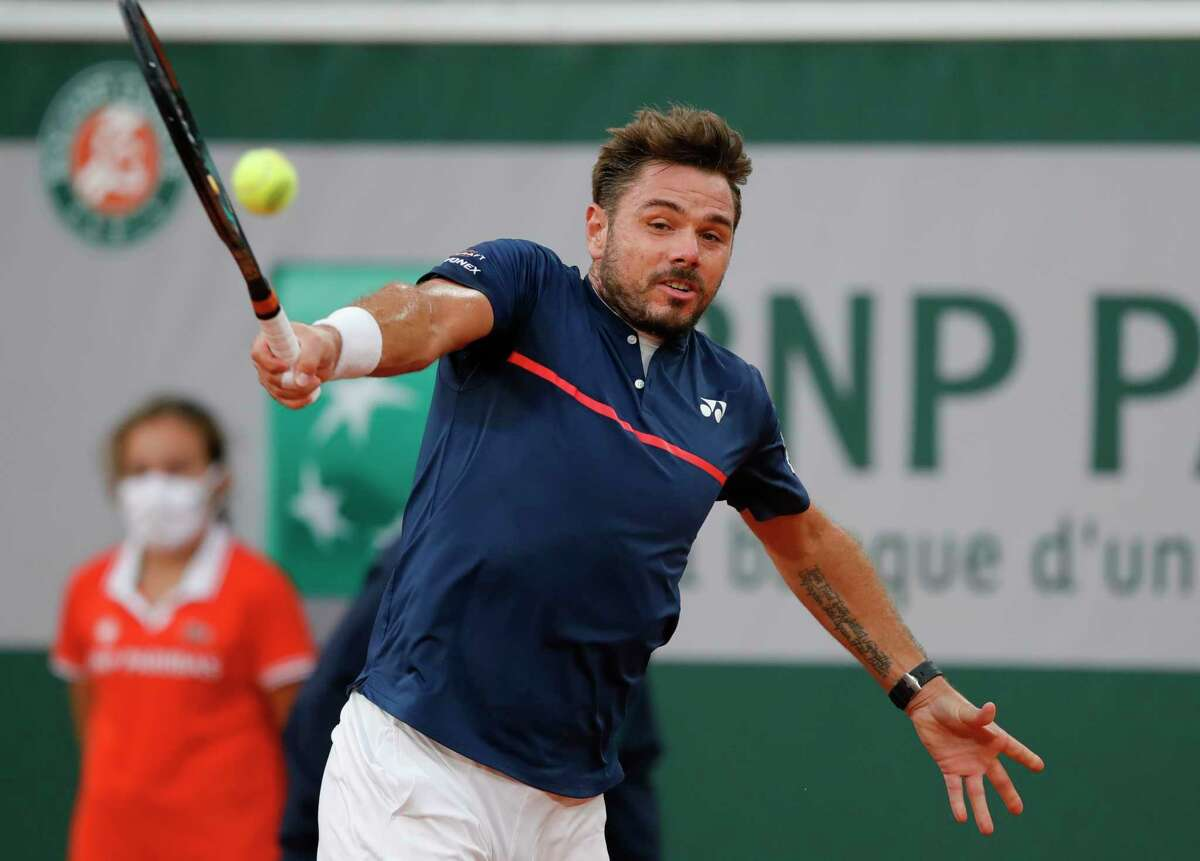 Switzerland's Stan Wawrinka plays a shot against Britain's Andy Murray in the first round match of the French Open tennis tournament at the Roland Garros stadium in Paris, France, Sunday, Sept. 27, 2020. (AP Photo/Christophe Ena)