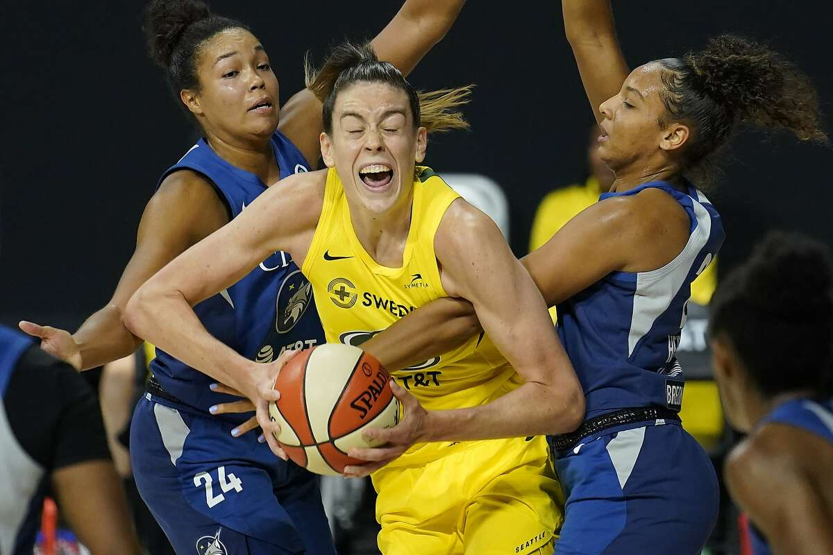 Seattle's Breanna Stewart (in yellow) is fouled by Minnesota's Mikiah Herbert Harrigan (21) on Sunday. Stewart scored 31 points to help her team complete a sweep of the semifinal series.