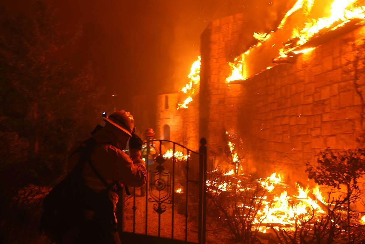 ST. HELENA, CALIFORNIA - SEPTEMBER 27: Firefighters walk through the burning Chateau Boswell Winery as the Glass Fire moves through the area on September 27, 2020 in St. Helena, California. The fast moving Glass fire has burned over 1,000 acres and has destroyed homes. Much of Northern California is under a red flag warning for high fire danger through Monday evening. (Photo by Justin Sullivan/Getty Images)