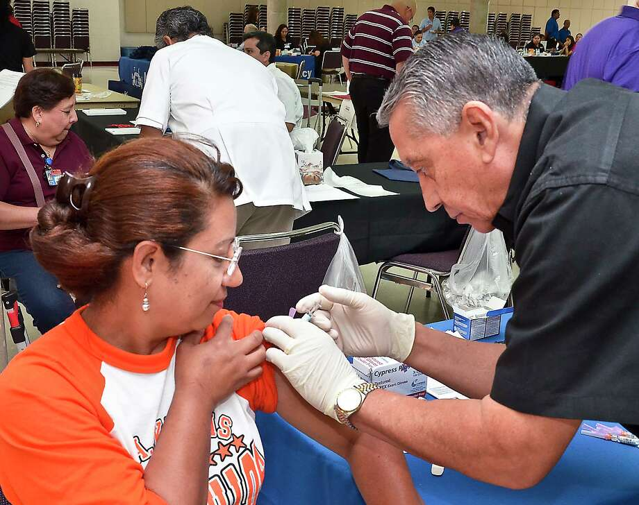 Kawas Elementary employee Mabel Cadena gets a flu shot from H-E-B Pharmacist Alvaro Liendo in August 2012, when Laredo ISD hosted a health fair for its employees as part of the district's Back to School Convocation. Photo: Cuate Santos /Laredo Morning Times File / LAREDO MORNING TIMES