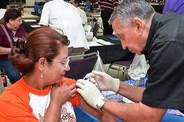 Kawas Elementary employee Mabel Cadena gets a flu shot from H-E-B Pharmacist Alvaro Liendo in August 2012, when Laredo ISD hosted a health fair for its employees as part of the district's Back to School Convocation.