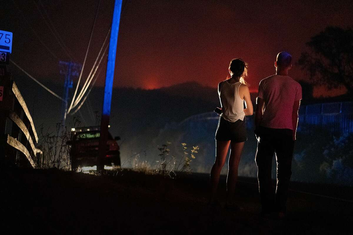 A couple watch the Glass fire from Calistoga Road on Sunday, Sept. 27, 2020 in Calistoga, Calif.
