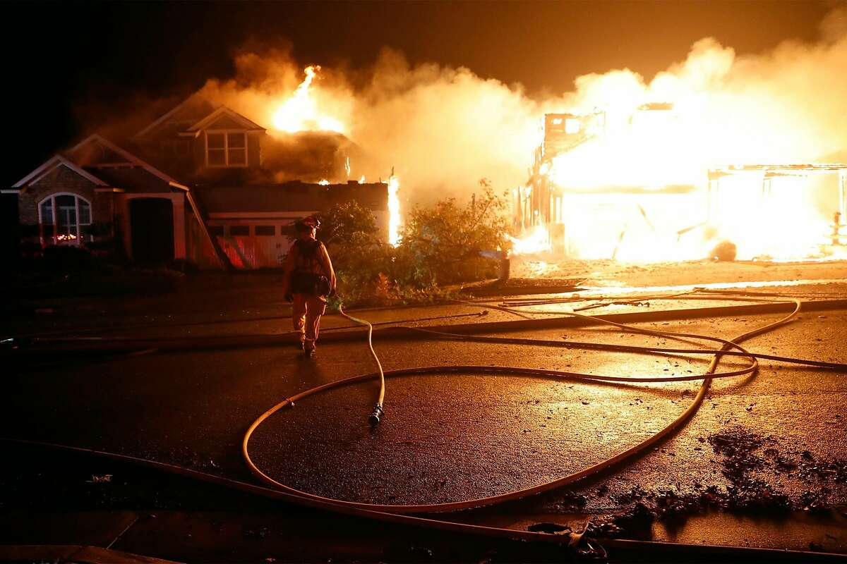 A firefighter watches as two houses burn on Mountain Hawk Drive as the Shady Fire burns in Skyhawk area of Santa Rosa, Calif., on Monday, September 28, 2020.