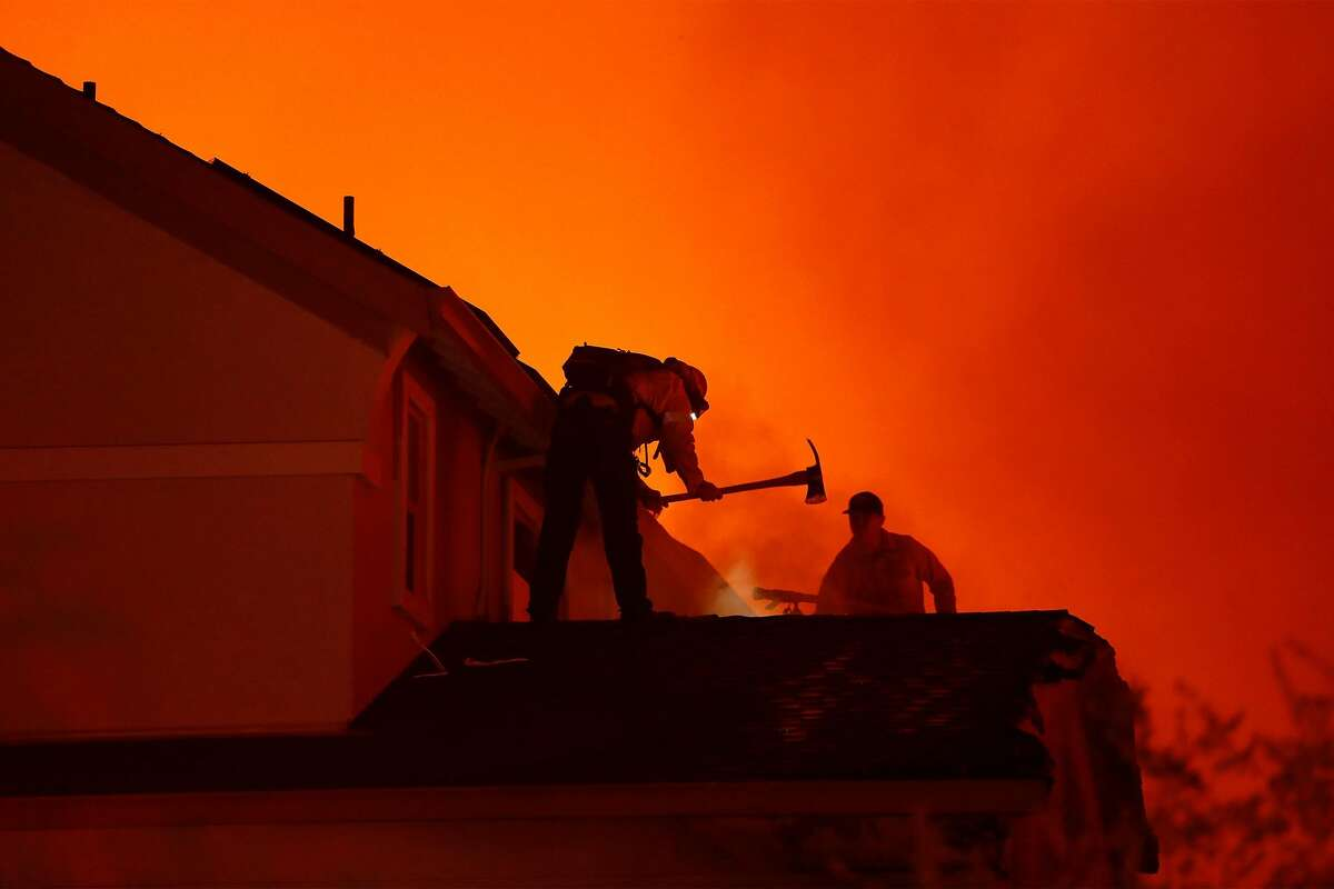 Two firefighters try to save a house as others burn on Mountain Hawk Way as the Shady Fire burns in Skyhawk area of Santa Rosa, Calif., on Monday, September 28, 2020.
