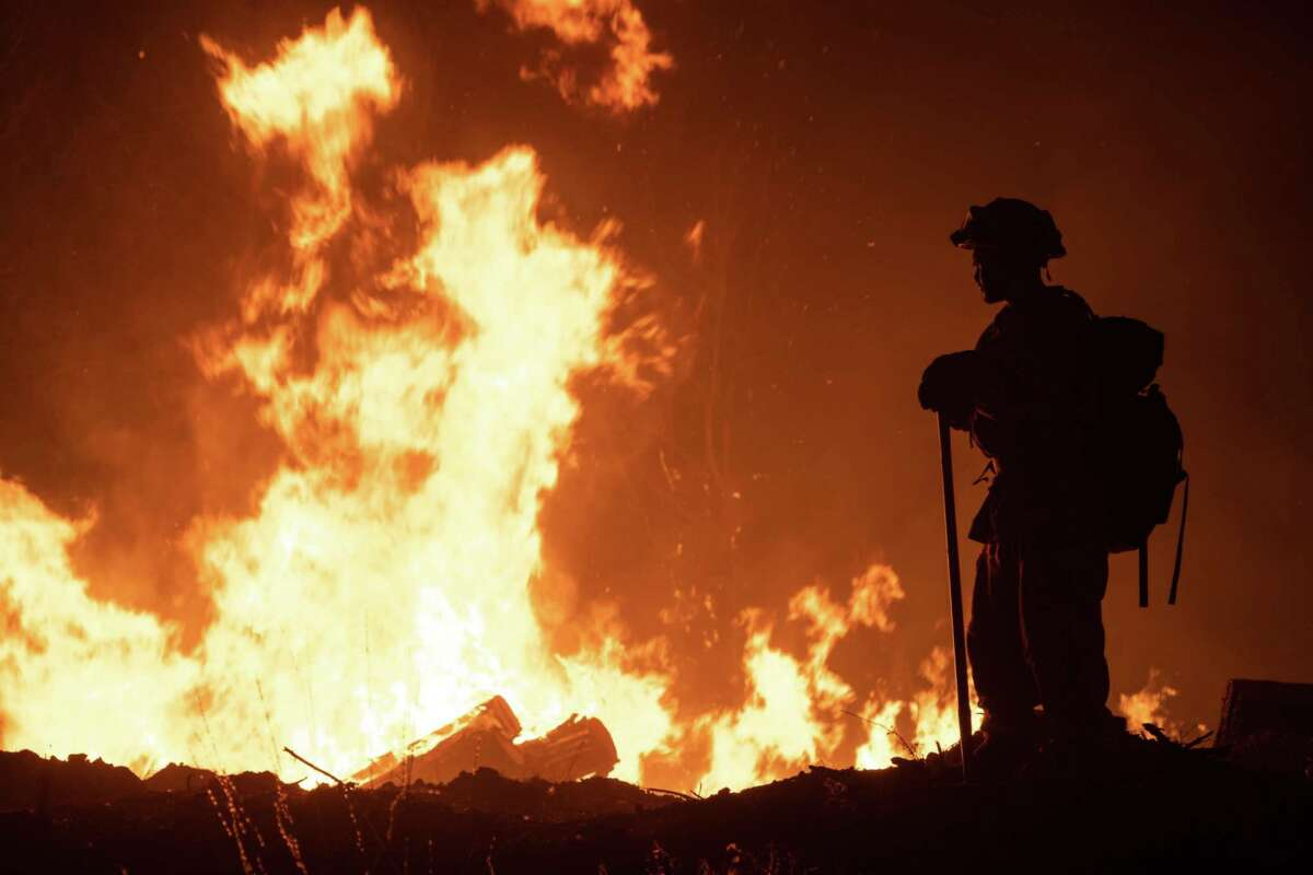 A firefighter monitors a firing operation to contain the Bear fire in Oroville, Calif., on Sept. 13, 2020.