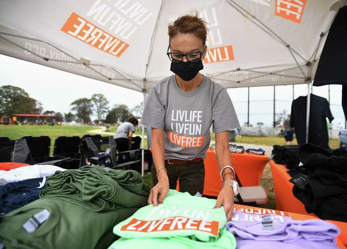 Sandy Rocha, of Bridgeport, puts out t-shirts for sale during the second annual LivFree charity baseball tournament at Seaside Park in Bridgeport, Conn. on Sunday, September 27, 2020. The organization raises money through athletic tournaments for pediatric cancer patients and their families.