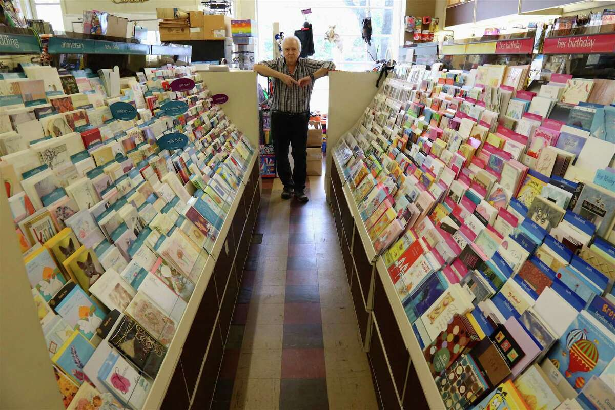 """Owner Bill Frate stands between aisles of greeting cards. Born in Darien in 1906, he was first elected to the state House of Representatives in 1948 and was known as """"Dean of the House"""" when he completed his 14th term in the spring of 1976. Locally, Gennaro Frate influenced the widening of Tokeneke Road and forwarded plans to construct the underpass beneath the railroad tracks on the Post Road. Before owning the Darien News Store, he served as caddy master and assistant golf pro at Wee Burn Country Club. He was an honorary member of the board of the Piedmont Club, a past member of the Noroton Fire Department, a member of the Darien Kiwanis Club, the Old Timers Association, and the Darien Chamber of Commerce."""