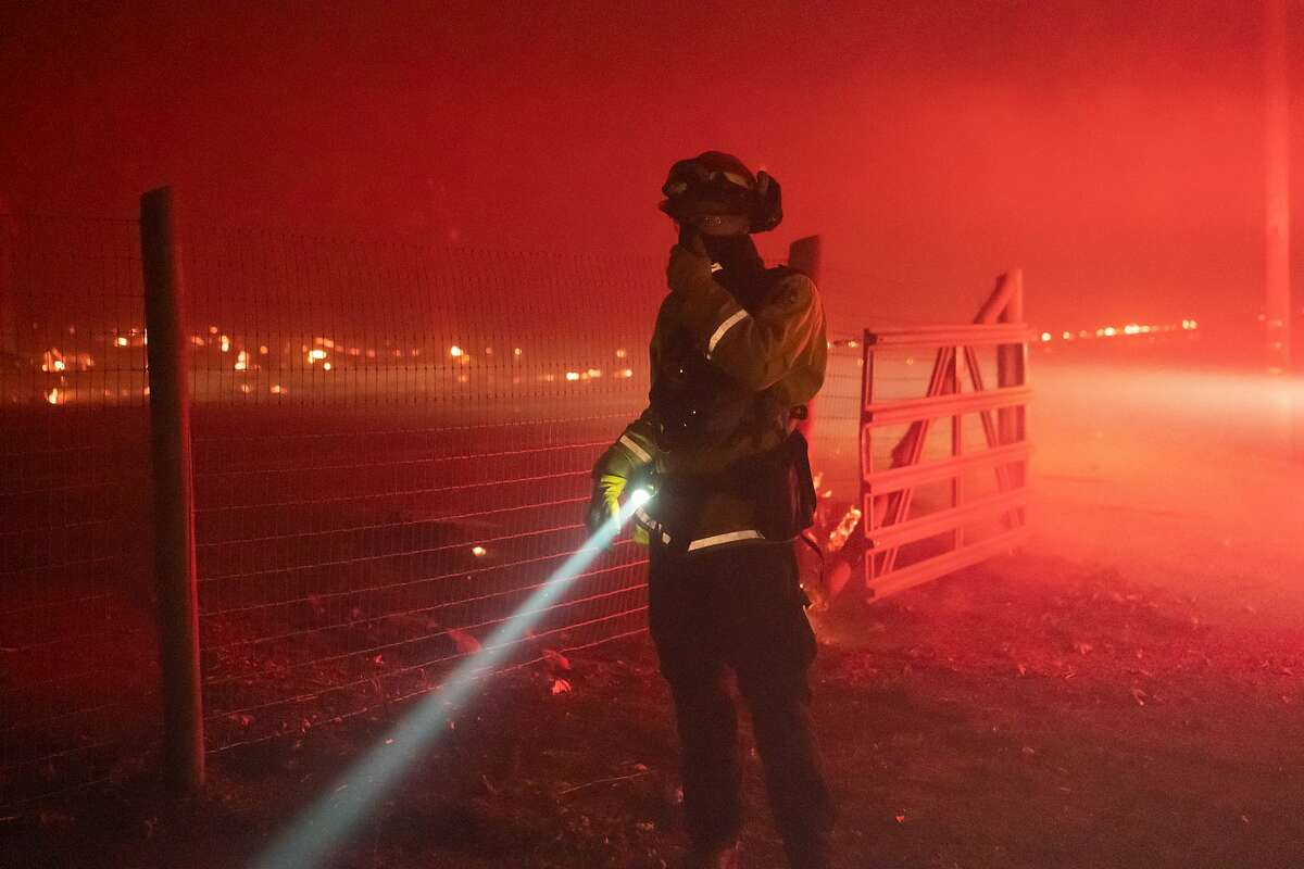 A firefighter looks over a fire threatening a house during the Glass on Monday, Sept. 28, 2020 in Santa Rosa, Calif.