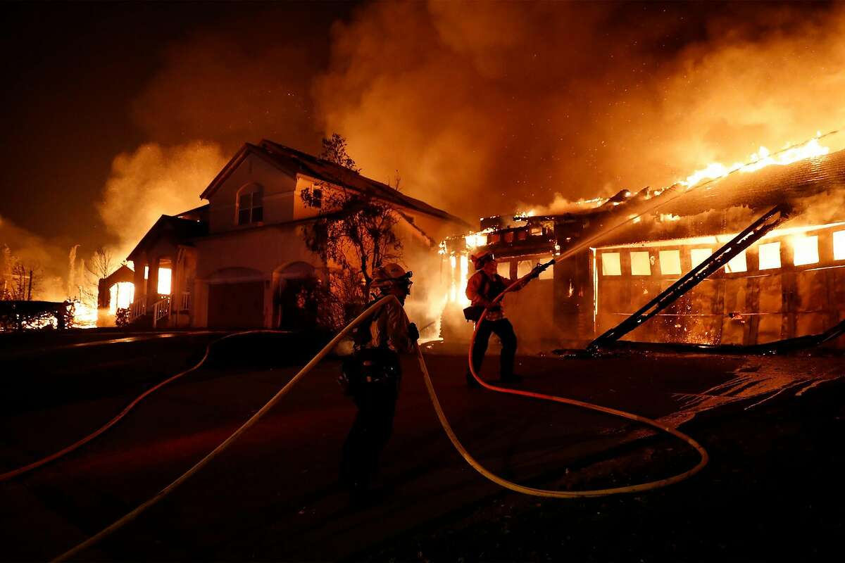 Firefighters try to keep house fires from spreading on Mountain Hawk Way in the Skyhawk area of Santa Rosa on Monday.
